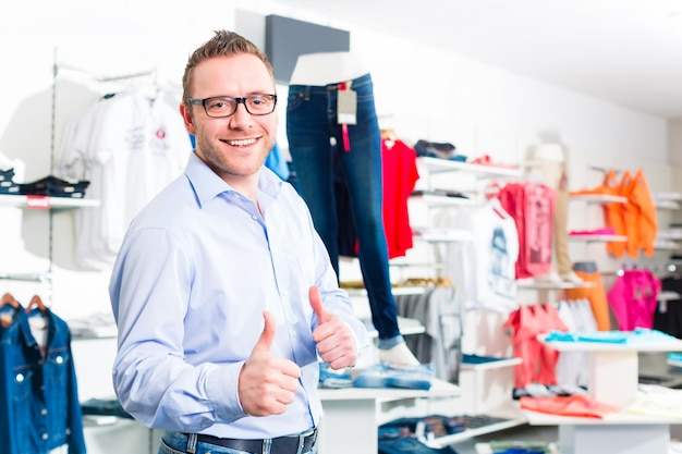 Gut aussehender mann, der blue jeans im shop oder im speicher kauft Premium Fotos