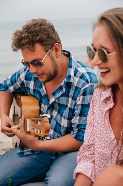 Gut aussehender mann, der eine gitarre spielt und ein lied für seine besten freunde singt Kostenlose Fotos