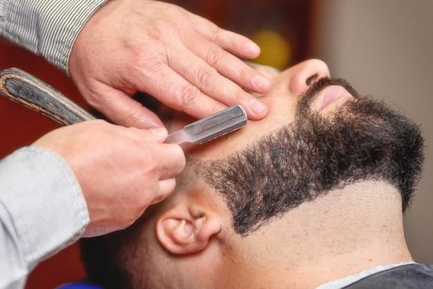 Gut aussehender mann, der eine rasur mit weinleserasiermesser am friseursalon hat. Premium Fotos