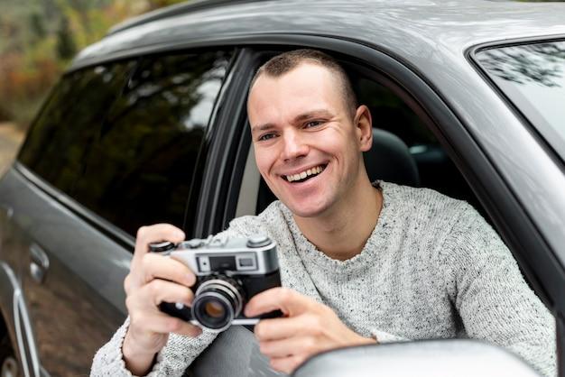 Gut aussehender mann, der eine weinlesekamera verwendet Kostenlose Fotos