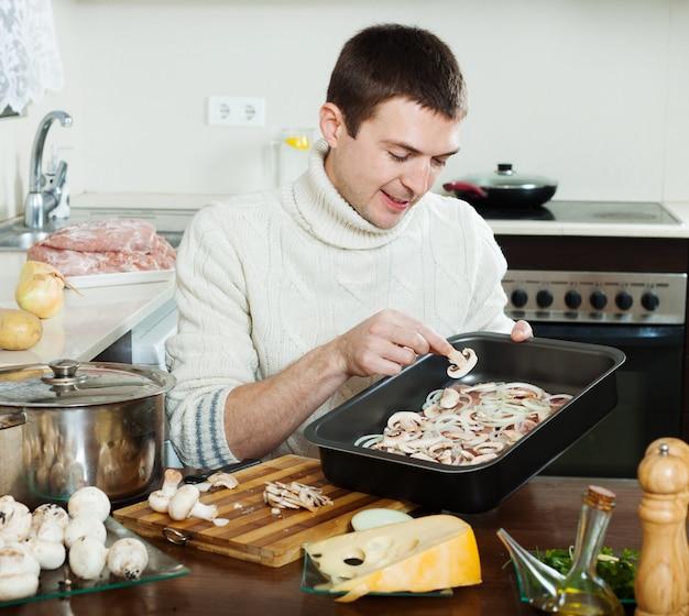 Gut aussehender mann, der fleisch mit pilzen kocht Kostenlose Fotos