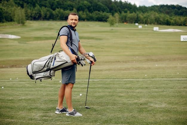 Gut aussehender mann, der golf auf einem golfplatz spielt Kostenlose Fotos