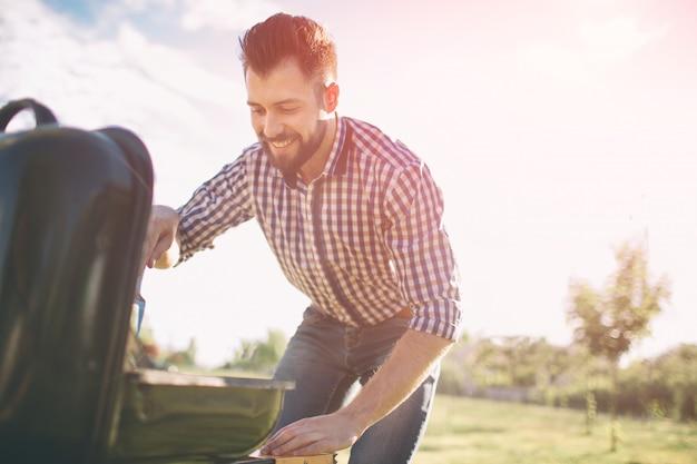 Gut aussehender mann, der grill für freunde vorbereitet. mann, der fleisch auf grill kocht - chef, der einige würste und pepperonis auf grill in den park im freien einsetzt - des essens im freien während der sommerzeit. Premium Fotos
