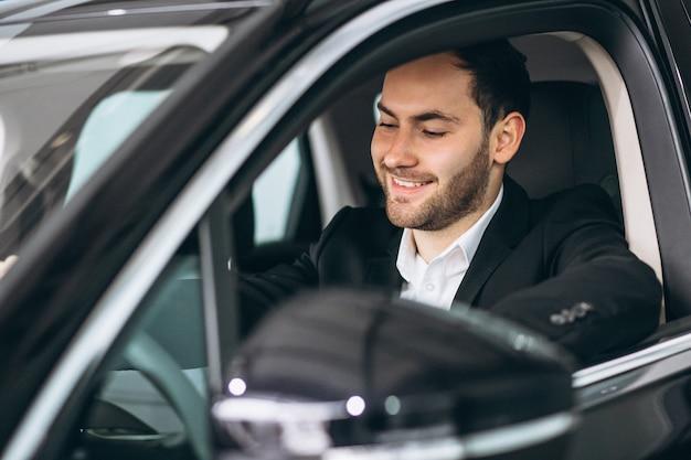 Gut aussehender mann, der im auto sitzt Kostenlose Fotos