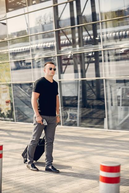 Gut aussehender mann, der im flughafen steht Kostenlose Fotos
