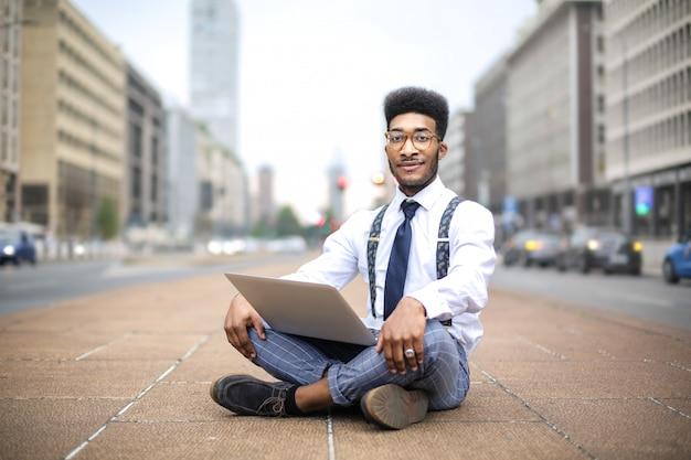 Gut aussehender mann, der in der straße, arbeitend mit seinem laptop sitzt Premium Fotos