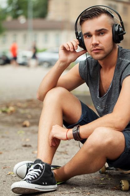 Gut aussehender mann, der in der straße mit kopfhörern sitzt Kostenlose Fotos