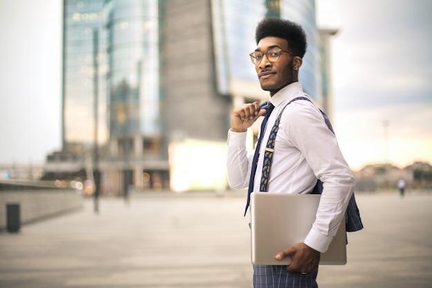 Gut aussehender mann, der in die straße, seinen laptop tragend geht Premium Fotos