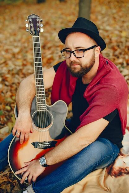 Gut aussehender mann, der in einem herbstpark sitzt Kostenlose Fotos