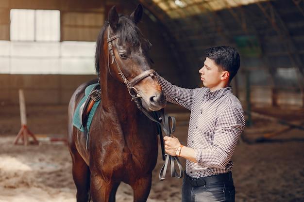 Gut aussehender mann, der in einer ranch steht Kostenlose Fotos