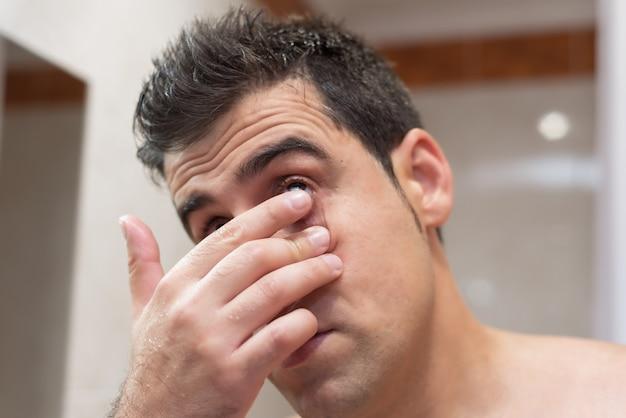 Gut aussehender mann, der kontaktlinse einfügt Premium Fotos