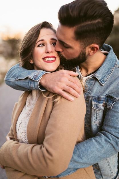 Gut aussehender mann, der lächelnde frau küsst Kostenlose Fotos