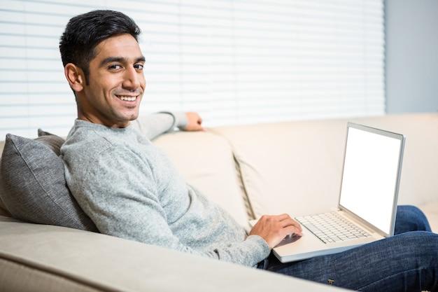 Gut aussehender mann, der laptop auf sofa verwendet Premium Fotos