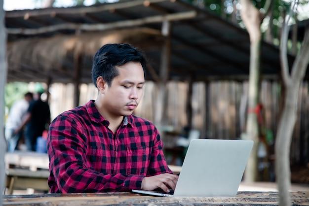Gut aussehender mann, der laptop in der reisenatur verwendet Kostenlose Fotos