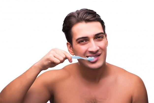 Gut aussehender mann, der seine zähne lokalisiert auf weiß putzt Premium Fotos