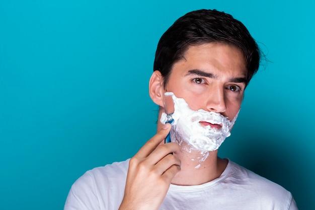 Gut aussehender mann, der seinen bart rasiert Kostenlose Fotos