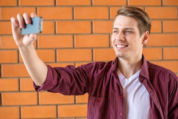 Gut aussehender mann, der selfie auf backsteinmauer macht. Premium Fotos