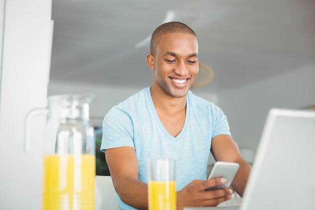 Gut aussehender mann, der smartphone in der küche verwendet Premium Fotos