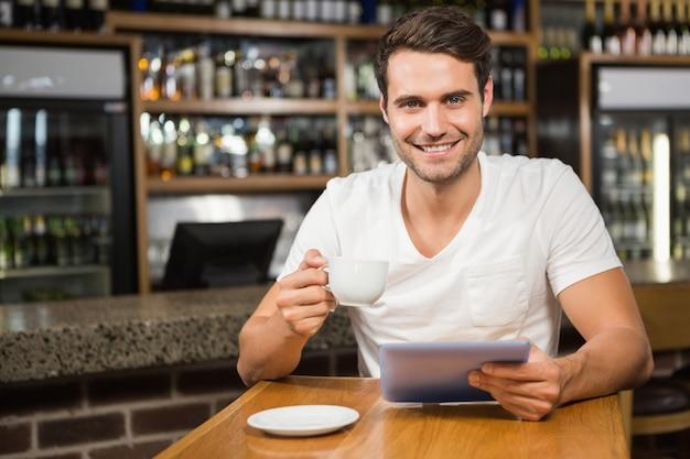 Gut aussehender mann, der tablette verwendet und kaffee trinkt Premium Fotos