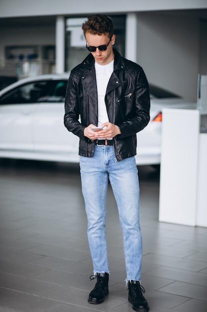 Gut aussehender mann, der telefon in einem autosalon verwendet Kostenlose Fotos