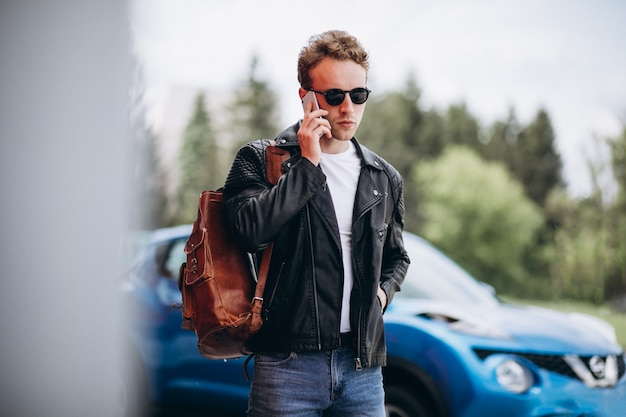 Gut aussehender mann, der telefon mit dem auto verwendet Kostenlose Fotos