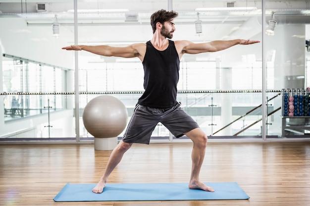 Gut aussehender mann, der yoga auf matte im studio tut Premium Fotos