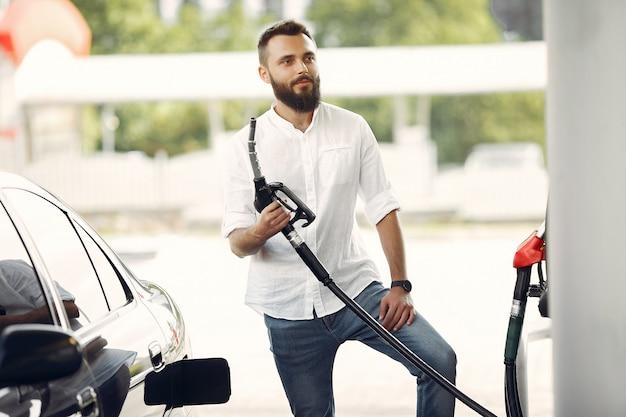 Gut aussehender mann gießt benzin in tank des autos Kostenlose Fotos