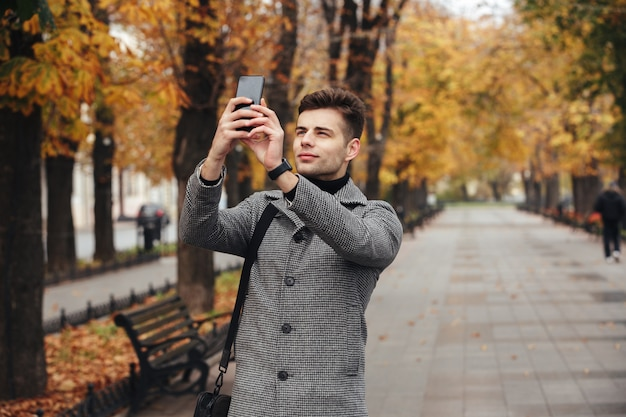 Gut aussehender mann im mantel, der foto von schönen herbstbäumen unter verwendung seines modernen mobiltelefons beim gehen in leeren park macht Kostenlose Fotos
