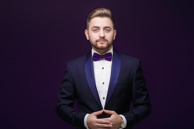 Gut aussehender mann im smoking und in fliege, die kamera betrachten. modische, festliche kleidung Premium Fotos