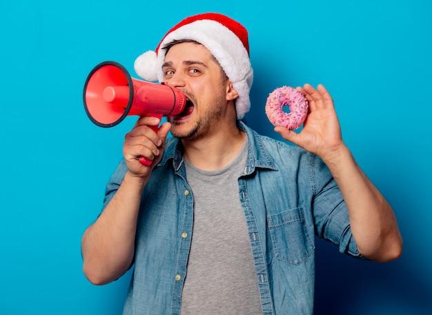 Gut aussehender mann im weihnachtshut mit donut und megafon Premium Fotos