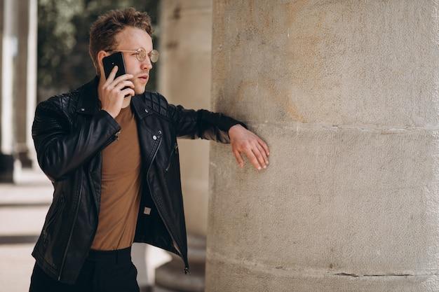 Gut aussehender mann in den schauspielen unter verwendung des telefons Kostenlose Fotos