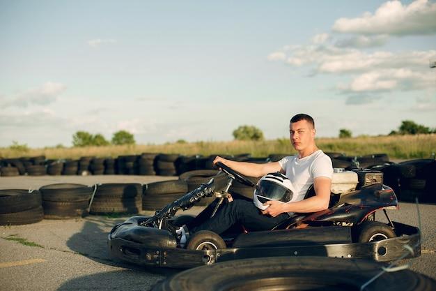 Gut aussehender mann in einem kart mit einem auto Kostenlose Fotos