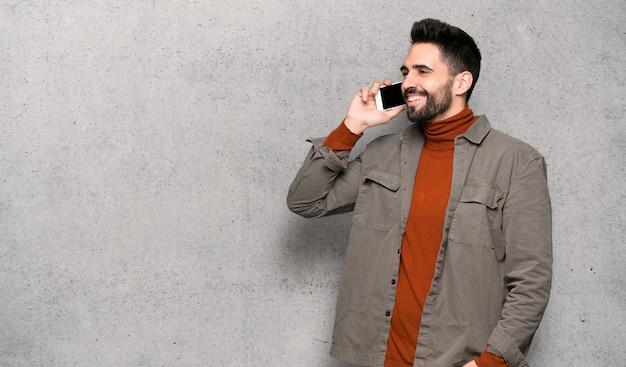 Gut aussehender mann mit bart, der ein gespräch mit dem handy über strukturierter wand hält Premium Fotos