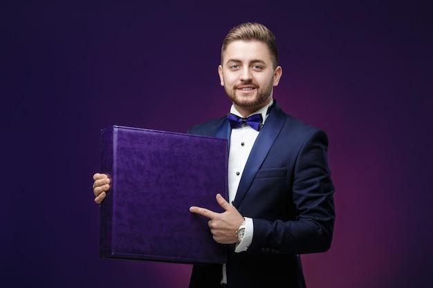 Gut aussehender mann mit bart im smoking hält großen kasten und an lächeln Premium Fotos