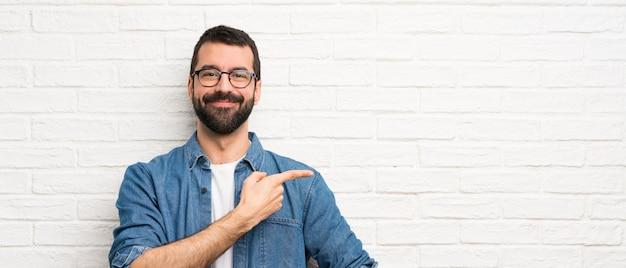 Gut aussehender mann mit bart über weißer backsteinmauer finger auf die seite zeigend Premium Fotos
