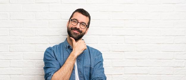 Gut aussehender mann mit bart über weißer backsteinmauer mit gläsern und dem lächeln Premium Fotos