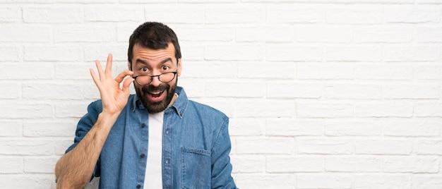 Gut aussehender mann mit bart über weißer backsteinmauer mit gläsern und überrascht Premium Fotos