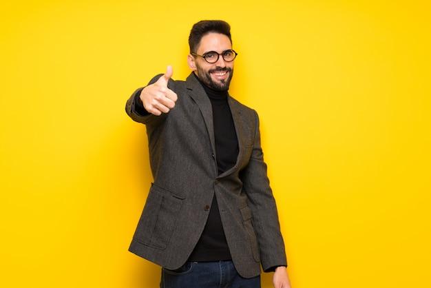 Gut aussehender mann mit brille geben daumen hoch geste, weil etwas gutes passiert ist Premium Fotos