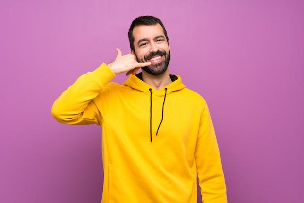 Gut aussehender mann mit dem gelben sweatshirt, das telefongeste macht. rufen sie mich zurück zu unterzeichnen Premium Fotos