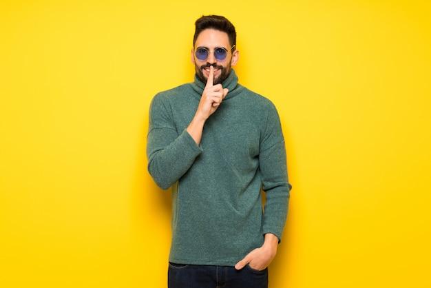 Gut aussehender mann mit der sonnenbrille, die ein zeichen der ruhegeste zeigt Premium Fotos