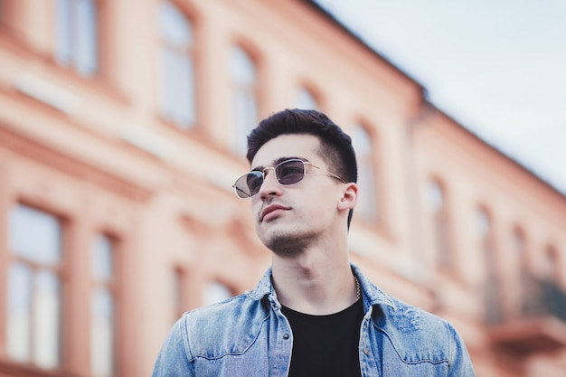 Gut aussehender mann mit der sonnenbrille, die in der stadt aufwirft Premium Fotos