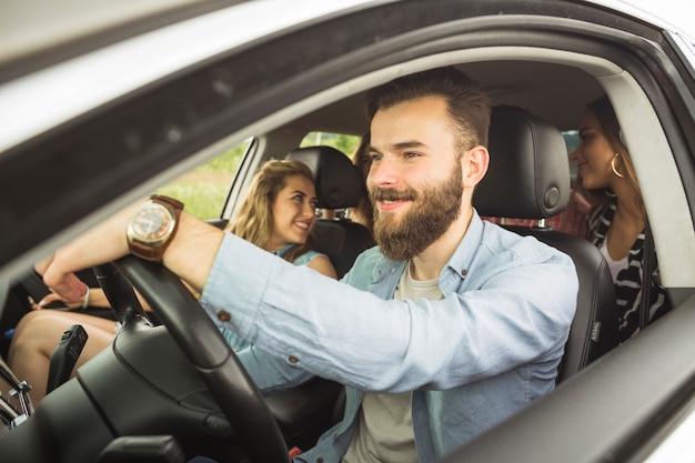Gut aussehender mann mit seinen freunden, die in auto reisen Premium Fotos