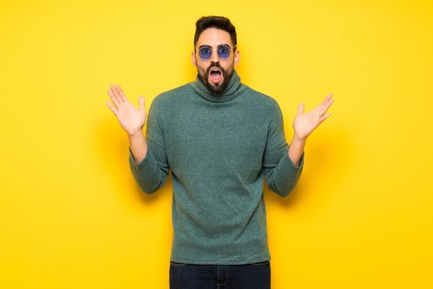 Gut aussehender mann mit sonnenbrille mit überraschung und entsetztem gesichtsausdruck Premium Fotos