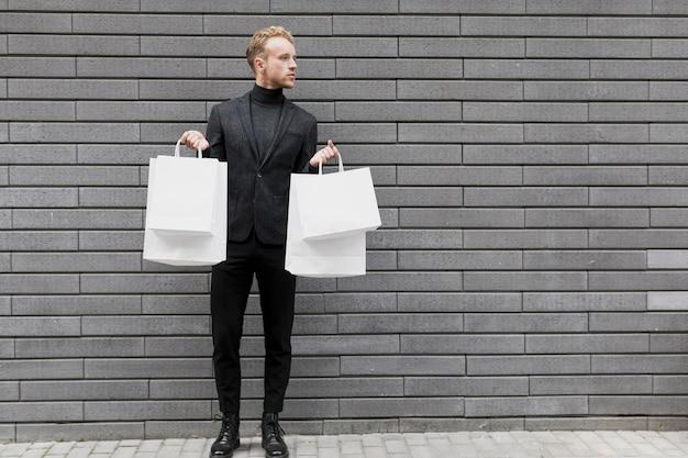 Gut aussehender mann mit weißen einkaufstüten Kostenlose Fotos