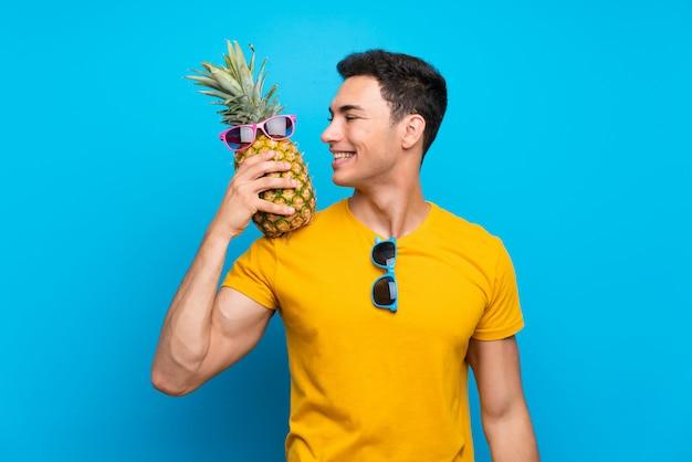 Gut aussehender mann über dem blauen hintergrund, der eine ananas mit sunglasse hält Premium Fotos