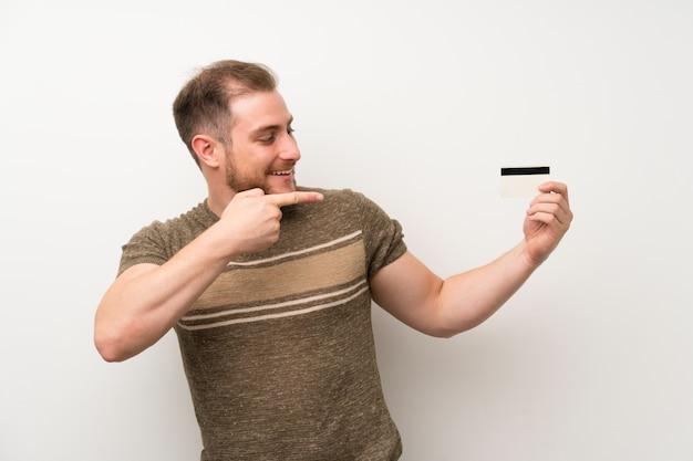 Gut aussehender mann über der lokalisierten weißen wand, die eine kreditkarte hält Premium Fotos