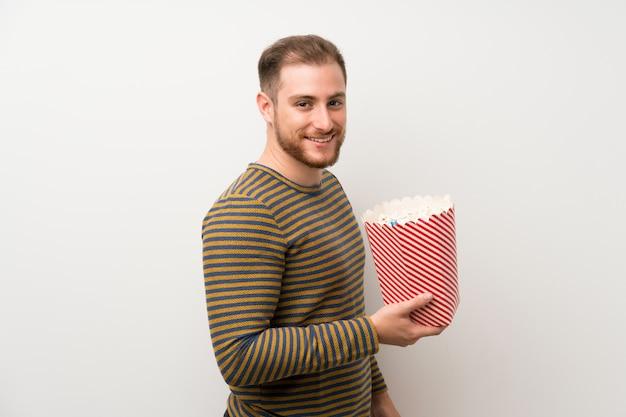 Gut aussehender mann über der lokalisierten weißen wand, die eine schüssel popcorn hält Premium Fotos