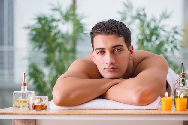Gut aussehender mann während des badekurortes, der sitzung massiert Premium Fotos