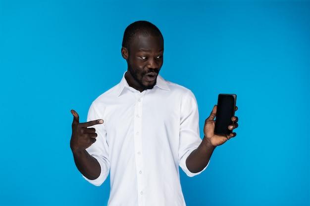 Gut aussehender mann zeigt auf das telefon Kostenlose Fotos