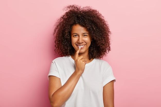 Gut aussehendes lustiges mädchen mit krausem afro-haar, lächelt breit, hält zeigefinger auf den lippen, bekommt interessante idee, denkt über großartigen plan nach, gekleidet in freizeitkleidung, modelle über rosiger wand Kostenlose Fotos